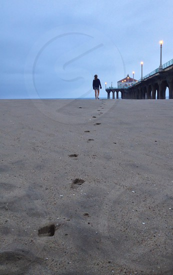 Young girl walking on beach by pier.  photo