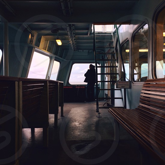 Person standing behind a staircase on a ferry photo