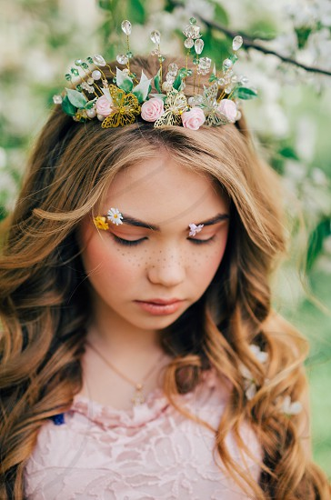 Portrait of young and beautiful girl with freckles on her face and flowers in her hair photo