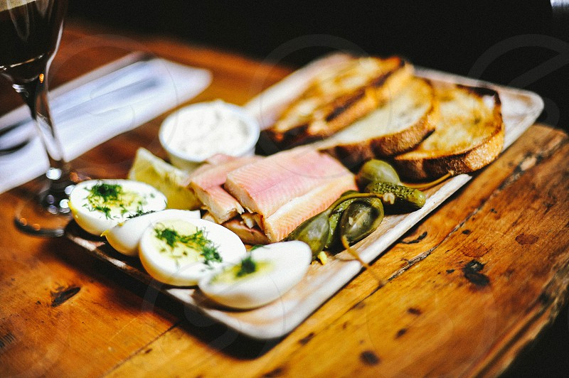 halved hard boiled eggs with seasoning sliced meat and toast with pickles and spread photo