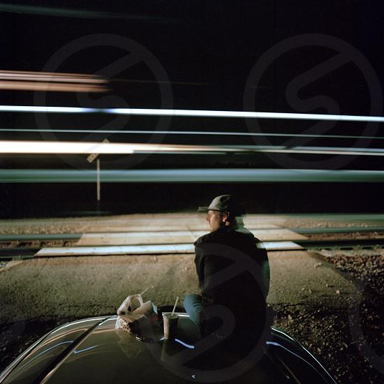 man sitting on car hood watching the train track photo