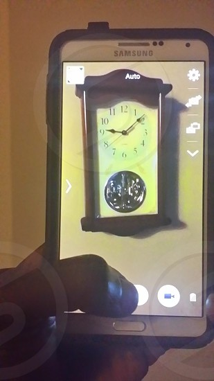 Taking a picture of the clock in the kitchen  photo
