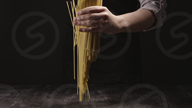 Raw natural flying vertical italian spaghetti from girl's hand on a kitchen table on a dark background. Slow motion Full HD video 240fps 1080p. Concept of italian food and cooking dinner. photo
