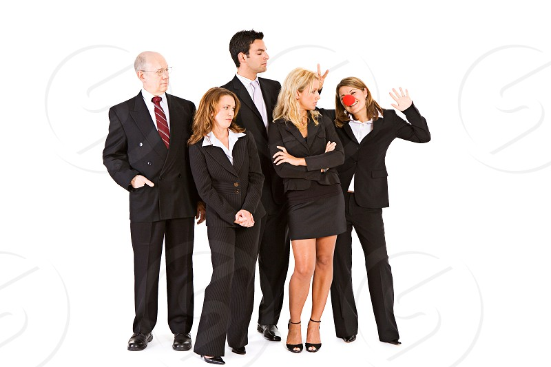 Business team annoyed at clown in group.  clown business businessman businesswoman team teamwork annoyed frustrated angry mad photo