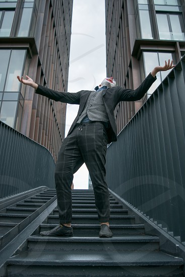 Male cosplayer crazy laughing standing on stairs in modern business district leaning his head back photo