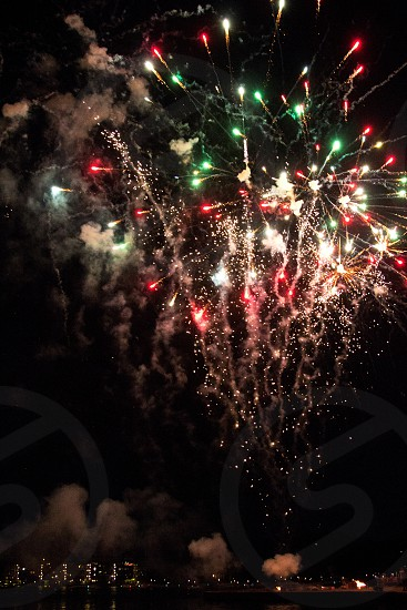 Red and green firework sparks in sky on black over lake photo