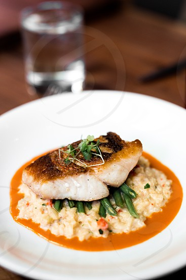 Snapper fish over gold pirloo and haricot verts. Vibrant and bright photo
