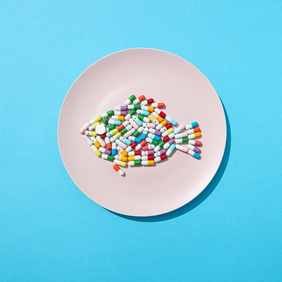 Different pills and supplements as food on round white plate in the form of fish on a blue background. Diet pills and supplements for dieting concept. Flat lay photo