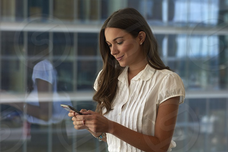 Successful business woman in a high rise office building standing at the window checking email messages on her mobile phone in bright daylight photo