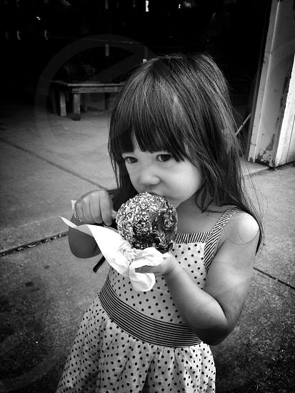 girl eating ice cream gray scale photography photo