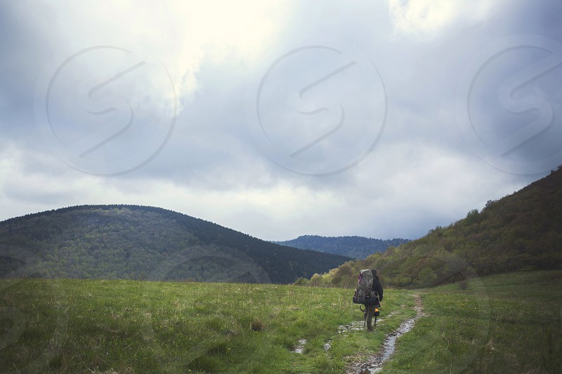 person with black hiking pack walking along dirt path road photo