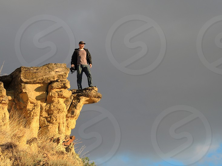 man standing on the edge of a rock photo