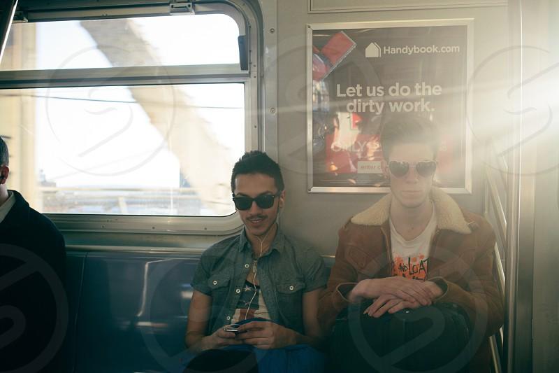 2 men sitting on public vehicle  photo