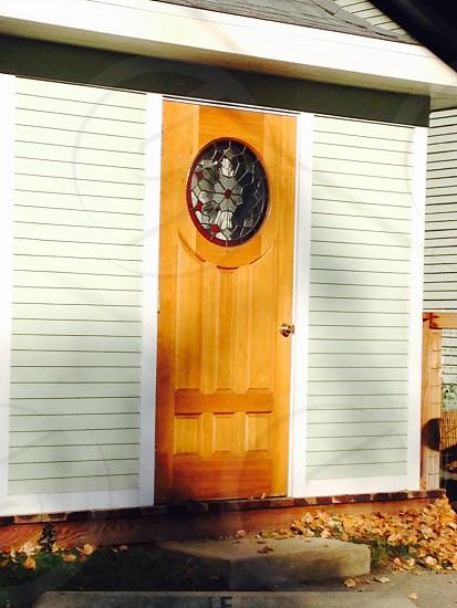 brown wooden door with round glass window photo