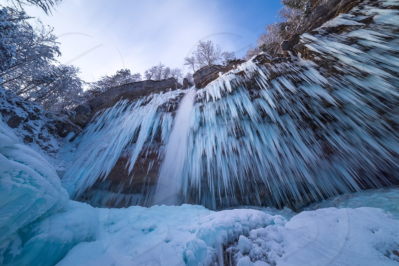 A long exposure photograph of a frozen Peričnik waterfall in Vrata valley Slovenia in winter. photo