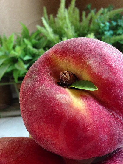 """Fresh"" A peach sits ripe on a kitchen counter. photo"