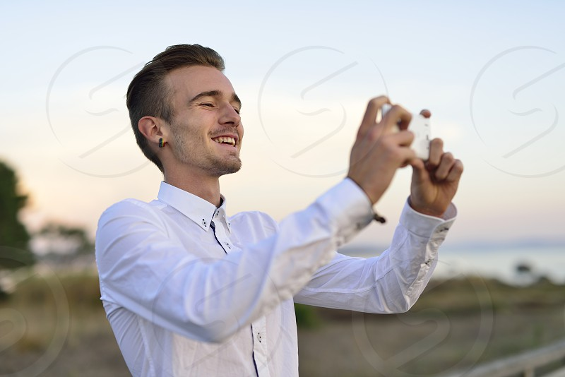 Young man photographing with mobile smartphone photo