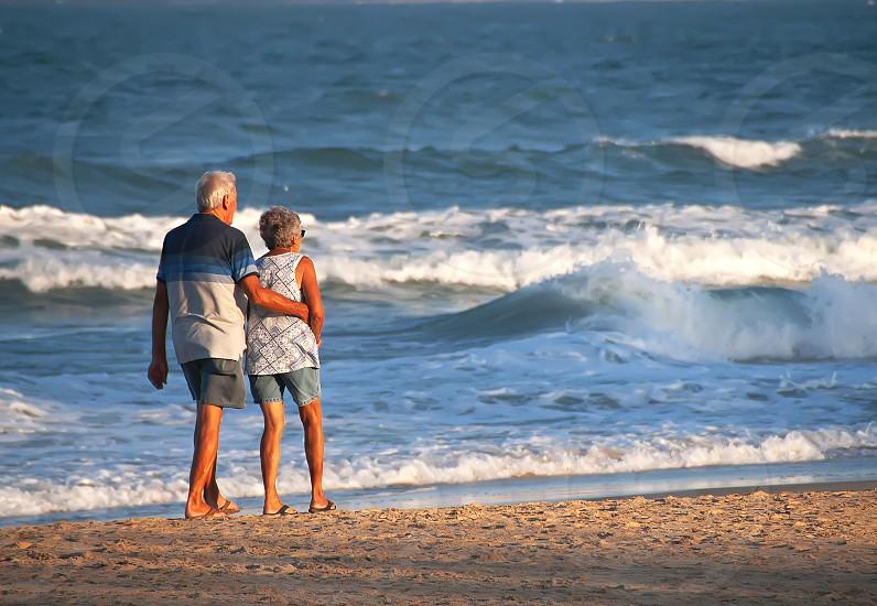 Old couple walking along a beach photo