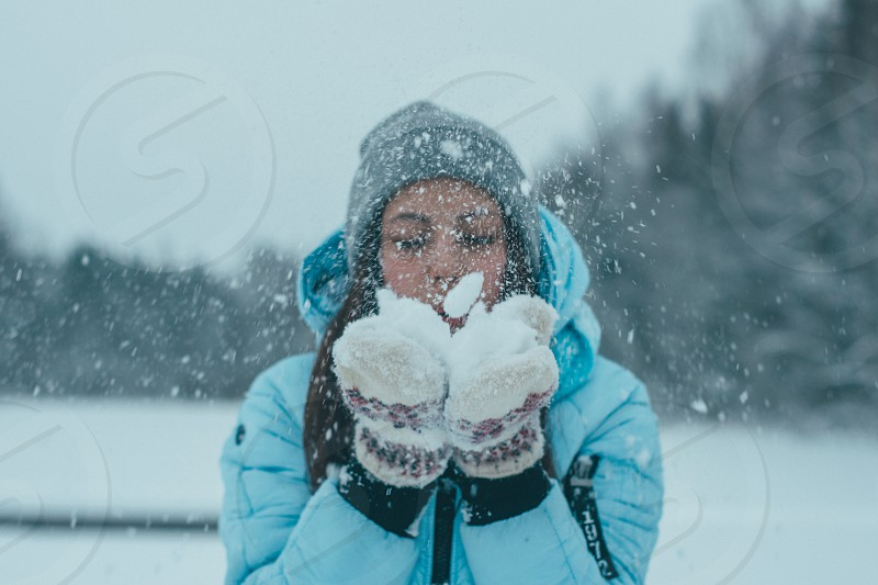 Girl blowing the snow off her palms photo