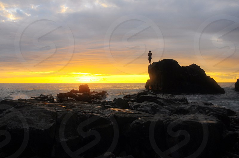 silhouette photo of a person standing on the rock in front of the sea during sunrise photo