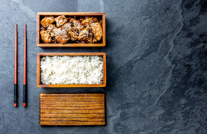 Japanese food. Chicken teriyaki with rice in wooden bento lunch box. slate background top view photo