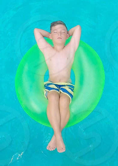 Boy in float in the pool at summer summertime photo