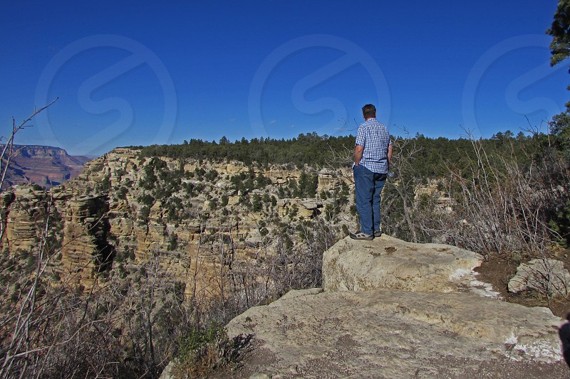Mid-aged man looking over the edge of the cliff photo