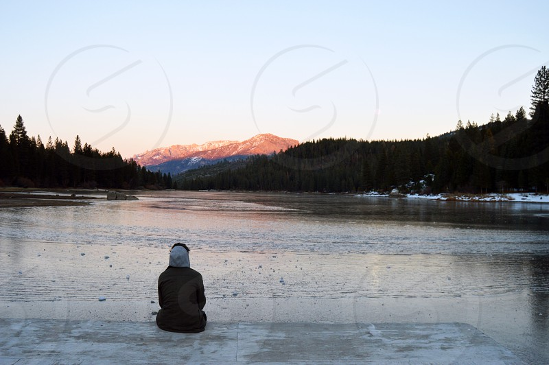 person sitting on dock beside body of water under blue sky during daytime photo