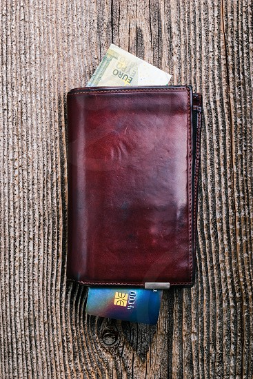Leather wallet with euro banknotes credit card on wooden desk. Portrait orientation photo