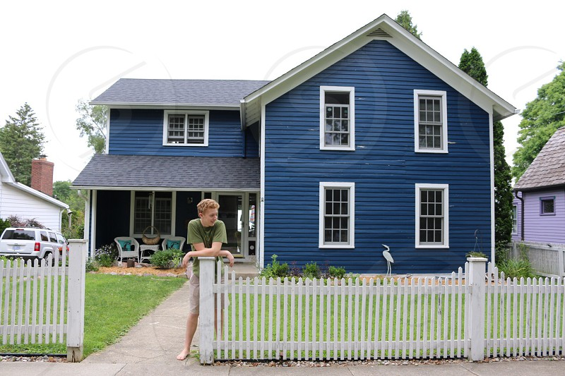 person leaning on white picket fence outside blue house photo