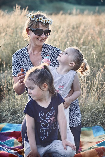 Family spending time together on a meadow close to nature. Parents and children playing together making coronet of wild flowers. Candid people real moments authentic situations photo