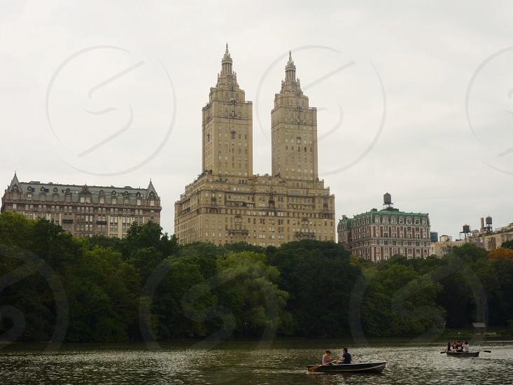 2 brown buildings behind green trees by green water with people riding boats photo