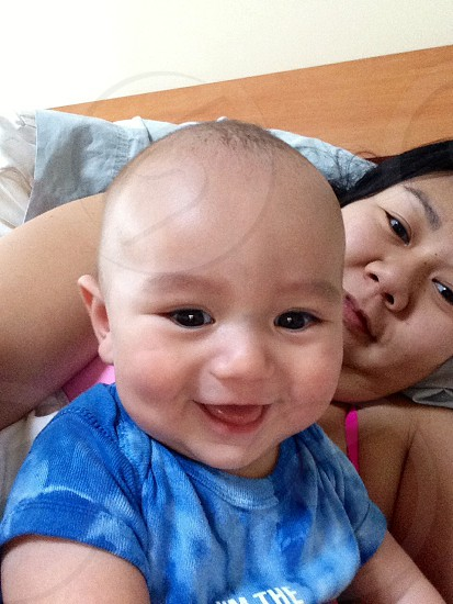 woman laying behind smiling baby in blue t shirt photo