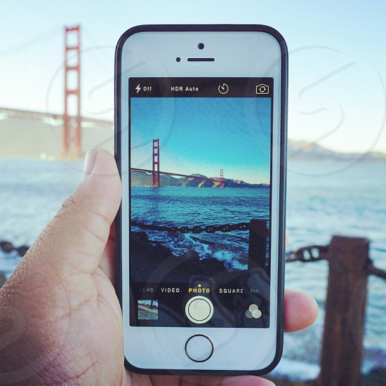 selective focus photograph of person holding iPhone 5s while taking photo of Golden bridge photo