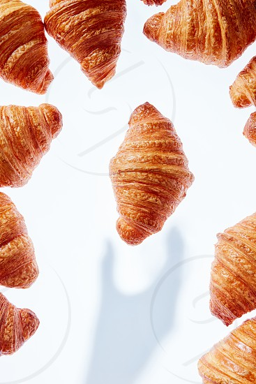 Fresh homemade delicious croissant with shadows from hand on a light background place for text. Food frame. Breakfast continental concept. photo