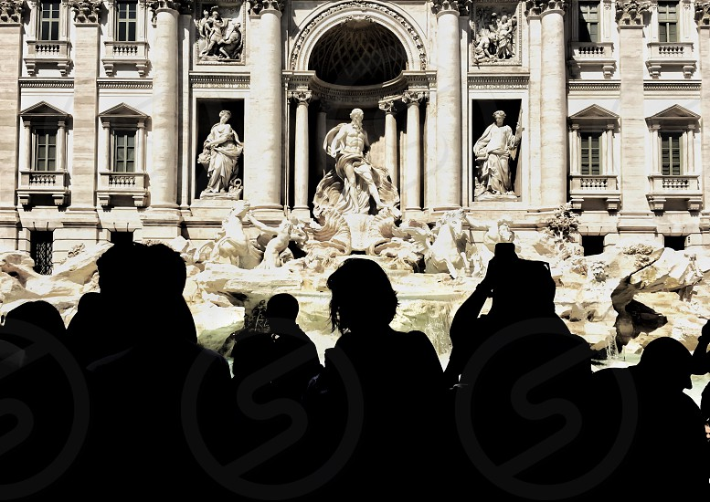 Tourists silhouettes shooting the wonderful Trevi fountain in Rome photo