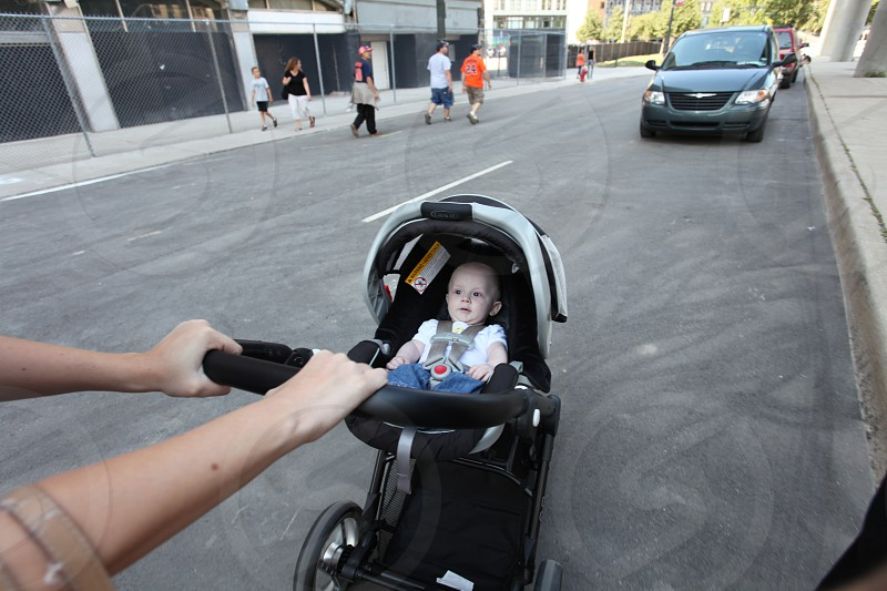 woman pushing baby in black stroller photo