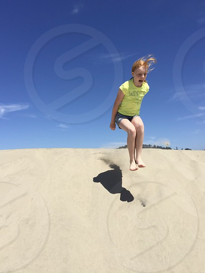 Child with Happy Fear jumping off sand dune photo