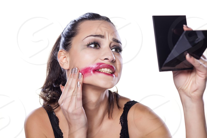 desperate beautiful girl removing her makeup by hand photo
