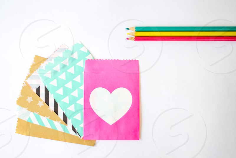 Colorful paper pencils hearts and patterns creative office desk photo
