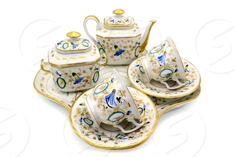 antique Biedermeier Time porcelain set with sugar box cups and teapot on a plate. flower ornaments. photo