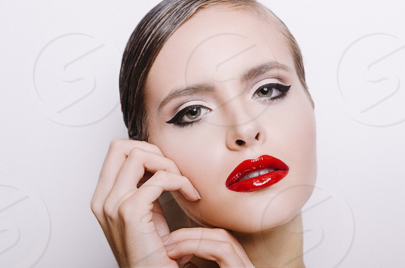 woman wearing red lip stain and black eyeliner touching her cheek photo