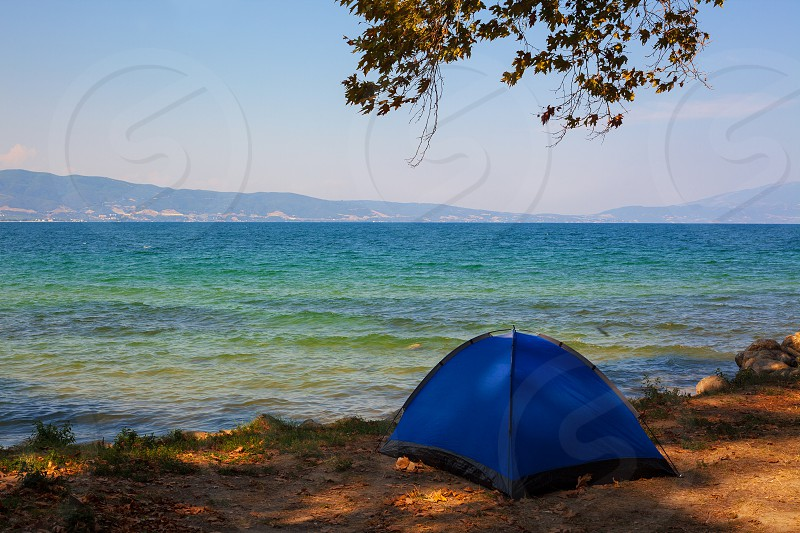Beach of Stavros town in Greece one blue tent under the trees with beautiful view on seaside.  photo