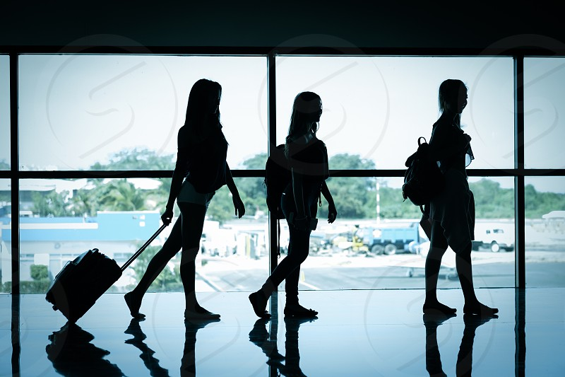 Silhouette of 3 female travelers at airport terminal photo