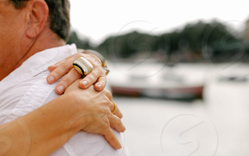 hands hugging a man in white shirt photo