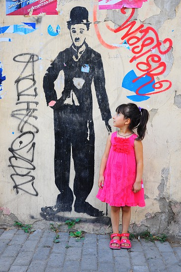 girl in pink tank dress standing near the wall photo