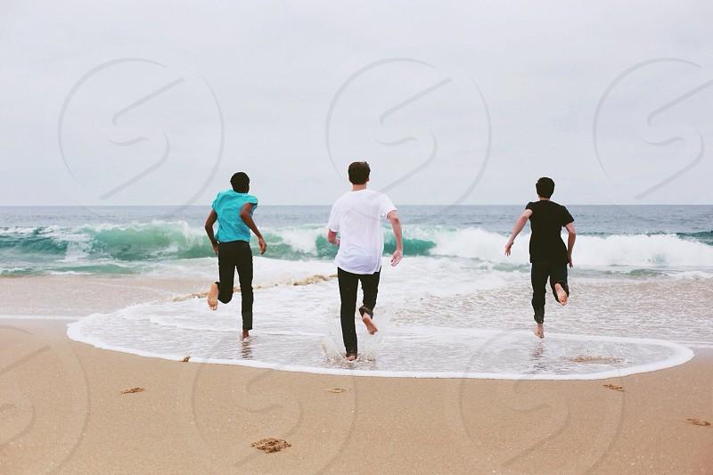 3 men running on seaside photo