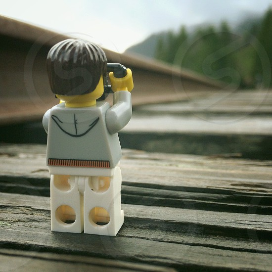 white and yellow lego character standing on black wooden surface photo