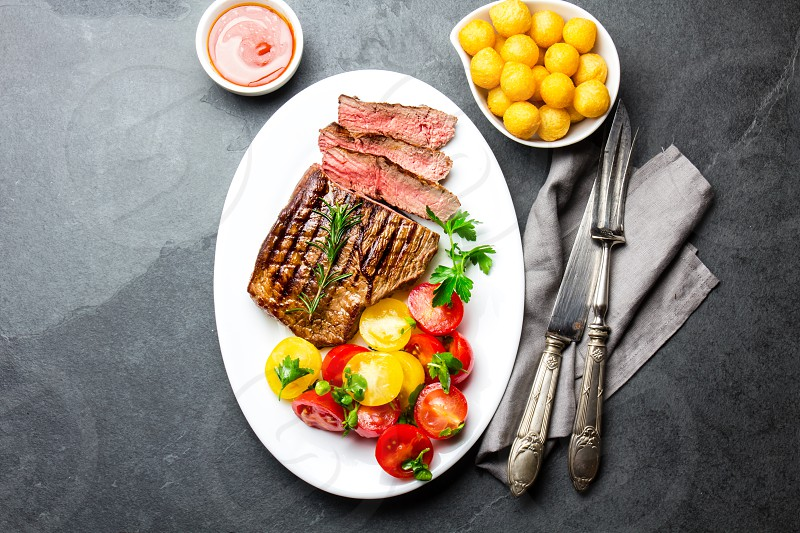 Sliced medium rare grilled beef steak served on white plate with tomato salad and potatoes balls. Barbecue bbq meat beef tenderloin. Top view slate background copy space. photo