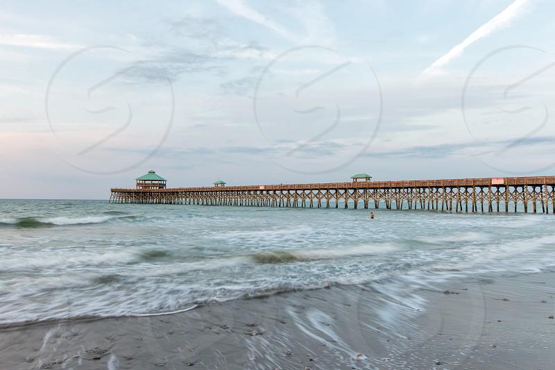 Ocean waves along Folly Beach pier in South Carolina. photo